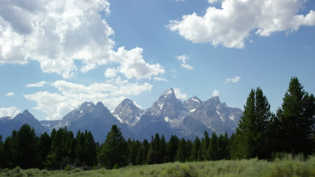moving shot of the grand teton mountains in grand teton national park in western wyoming on a sunny day - grand teton stock videos & royalty-free footage