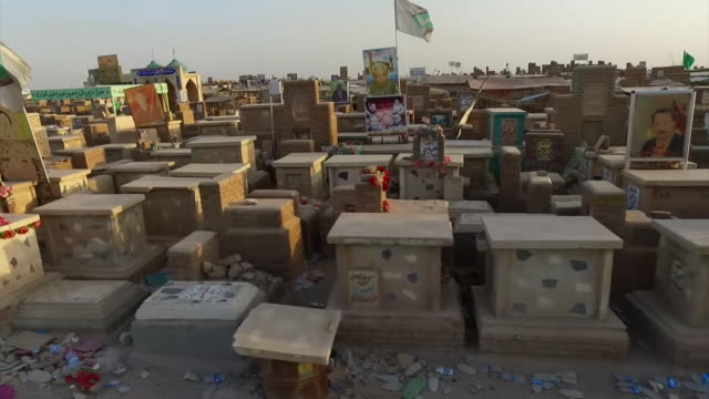 moving shot past graves in wadi al-salaam cemetery, the largest in the world, in najaf, iraq - najaf stock videos & royalty-free footage