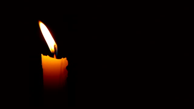 hd moving single lit candle flame in the wind - candle stock videos and b-roll footage