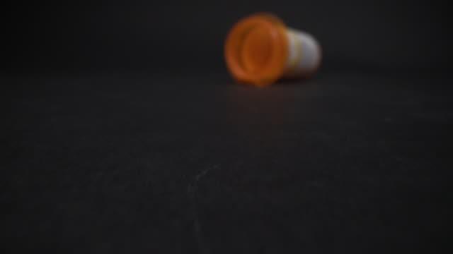 コピースペースを持つ黒いスタジオの背景に空の処方箋ボトルのスライダーショットを移動 - 注意欠陥過活動性障害点の映像素材/bロール