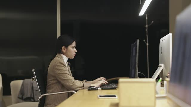Movendo vídeo em câmera lenta de colegas de trabalho masculinos e femininos diversos trabalhando até tarde da noite