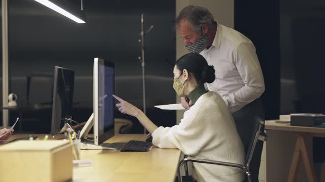 Movendo vídeo em câmera lenta de diversos designers masculinos e femininos trabalhando até tarde da noite no tempo do COVID-19