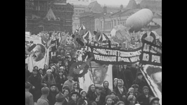 moving through moscow street during may day parade, with posters of soviet leaders, banners, and soviet stars / military parade with marching... - ex unione sovietica video stock e b–roll
