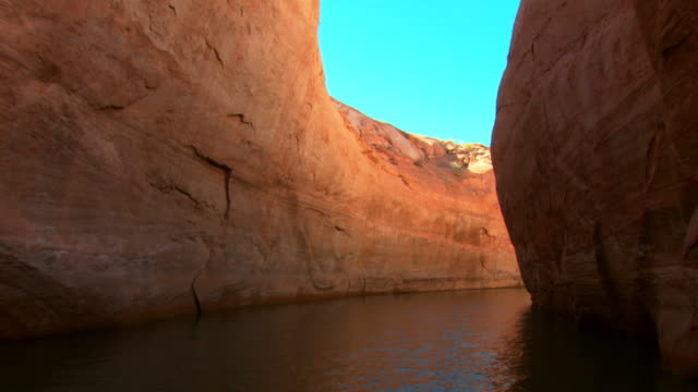 pov, moving through narrow inlet between rock formations, lake powell, glen canyon national recreation area, utah, usa - lago powell video stock e b–roll