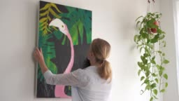 Moving to a new home. A young blonde woman laying down a picture on canvas in a room.
