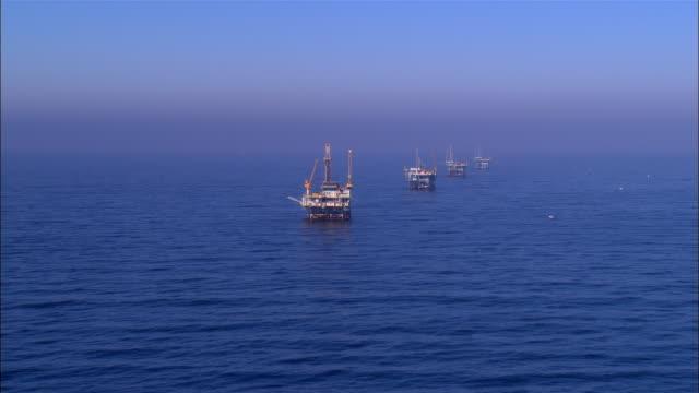 aerial moving toward row of oil rigs/ oh rig/ santa barbara, california  - offshore platform stock videos & royalty-free footage