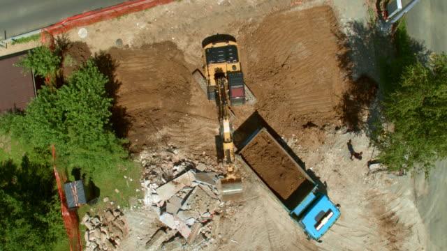 vídeos de stock e filmes b-roll de aerial moving towards an excavator loading a truck with soil at the construction site - veículo de construção