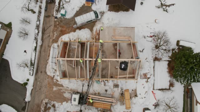 aerial moving towards the crane lifting a supportive beam to the rooftop - construction site stock videos & royalty-free footage