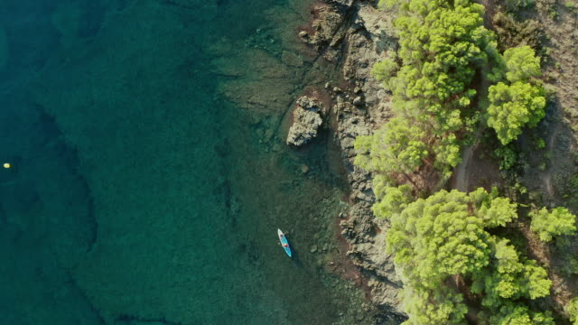 moving up aerial video of couple kayaking along the mediterranean coast - pagaiare video stock e b–roll