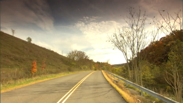 Driving on two way road on country side Autumn colored hills trees on both sides Very scenic tranquil journey soul searching soul search Fall...