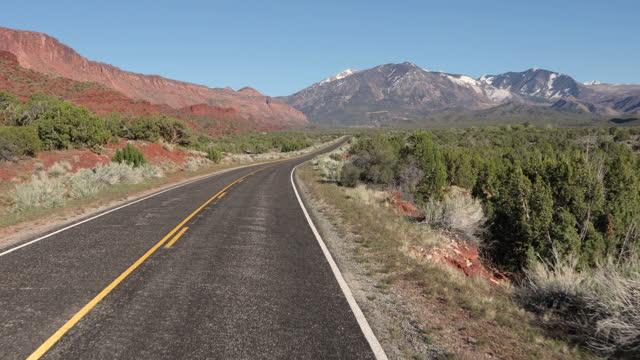 bewegende fahrzeugperspektive des fahrens auf der wüstenautobahn - moab utah stock-videos und b-roll-filmmaterial