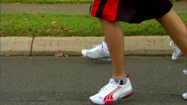 two males wearing shorts running sneakers running jogging on wet street pavement - running shorts stock videos & royalty-free footage
