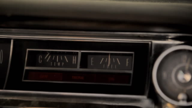 a moving vehicle's dashboard displays a fuel gauge and a temperature indicator. - vecchio stile video stock e b–roll