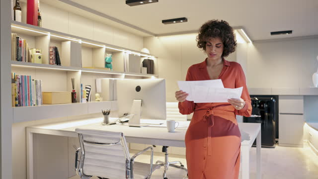 Moving Video of Female Business Professional Looking at Document in Office