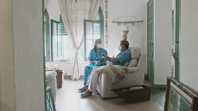 vídeos y material grabado en eventos de stock de video en movimiento de la enfermera y el hombre mayor que usan máscaras durante la llamada a la casa - visita