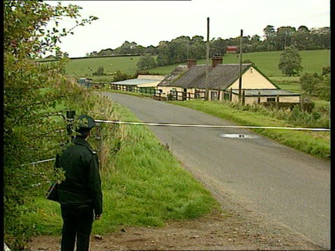 moy - double murder; northern ireland: co tyrone: moy: tbv policeman zoom in farmhouse where bodies of charles and theresa fox were found murdered - ulster province stock videos & royalty-free footage