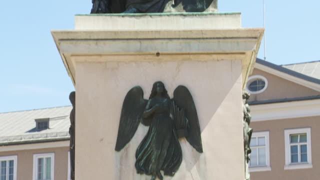 vídeos de stock e filmes b-roll de tilt up mozart monument in mozartplatz (mozart square) in salzburg - figura feminina
