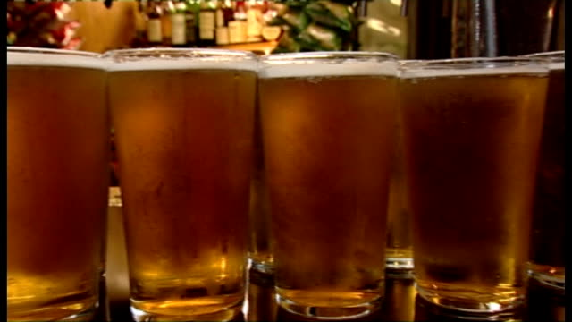 mps call for revised guidelines on safe alcohol drinking; england: london: int speeded up bar lady putting 14 pints of lager onto bar table pints of... - lager stock videos & royalty-free footage