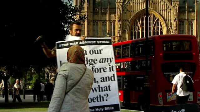 vídeos de stock, filmes e b-roll de mps debate military action in syria westminster ext protesters with 'stop war against syria' and 'hands off syria' placards opposite houses of... - stop placa em inglês