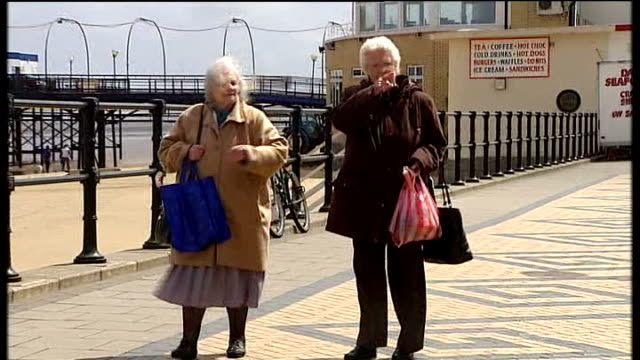 impact on voters two elderly ladies along promenade middleaged couple arminarm along promenade hand paying coins as takes packet of sweets from vendor - arm in arm stock videos & royalty-free footage