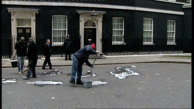 reports that allowances review may not recommend pay rise ENGLAND London Downing Street EXT Various shots cleaners scrubbing paint from road outside...