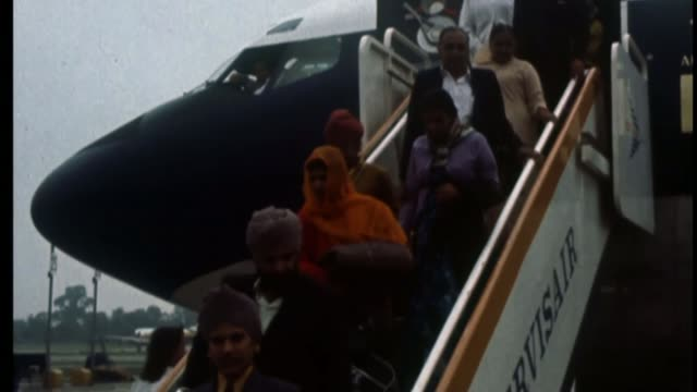mps led by chuka umunna propose new immigration system fs091072004 / tx stanstead airport ugandan asian refugees down steps from plane double decker... - 1972 stock videos & royalty-free footage