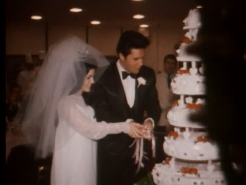 mr. and mrs. elvis and priscilla presley cut their wedding cake. - プリシラ プレスリー点の映像素材/bロール