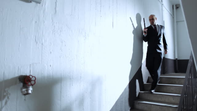 mr. evil walks down staircase with silenced gun - assassination stock videos and b-roll footage