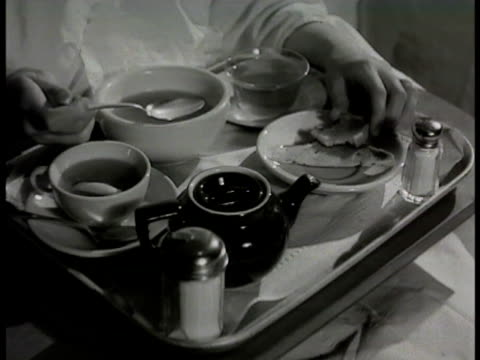 stockvideo's en b-roll-footage met 'mrs conrad' in hospital bed eating soup broth tea toast on tray restricted diet nurse giving pill to 'mrs conrad' taking pill drinking water... - 1948
