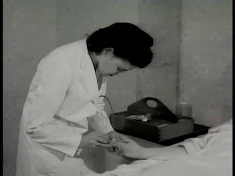 'mrs conrad' reclined in hospital bed female technician pricking 'mrs conrad' finger placing pen shaped instrument to finger end attached to mouth... - 1948 stock-videos und b-roll-filmmaterial
