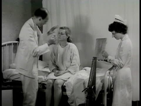 'Mrs Conrad' sitting on hospital bed Doctor examining eyes throat CU Doctor checking reflexes w/ knee tap reflex test nurse taking notes