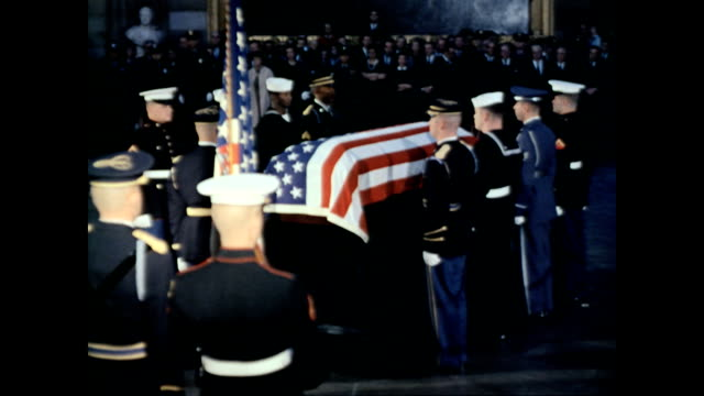 mrs jackie kennedy and attendants pay respects to president kennedy before his coffin leaves the capitol building / soldiers lift the president's... - 棺点の映像素材/bロール