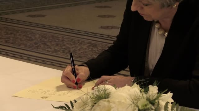 Mrs May visited Manchester town hall to read tributes and sign a book of condolence as people began gathering outside for a vigil in Albert Square