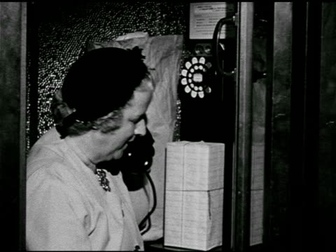 DRAMATIZATION MS 'Mrs Norton' using public pay phone booth hanging up receiver gathering packages passing man waiting to make call male in hat...