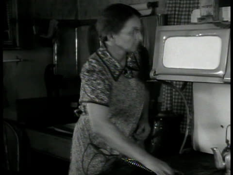 mrs. witham' pumping water. int mrs. witham stoking stove. ext boy picking potatoes. basket. int ernest witham' listening to radio. scattered farm... - housework stock videos & royalty-free footage