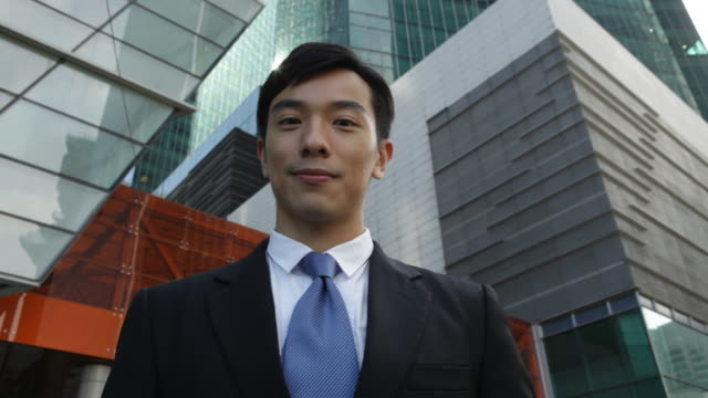 m/s businessman smiling to camera in front of buildings