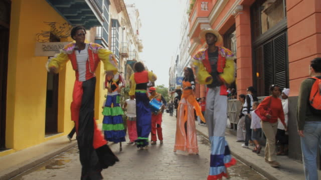 stockvideo's en b-roll-footage met ms zi cuban performers perform on stilts and dance on streets of cuba / havana, cuba - cuba