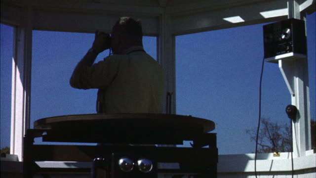 Ms Forest ranger in tower scans horizon with binoculars / Canada