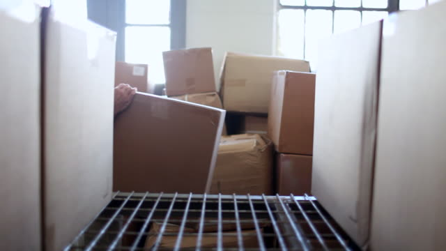 "vídeos y material grabado en eventos de stock de ""ms man placing box in empty space on shelf full of boxes / brooklyn, new york, united states"" - posicionamiento"