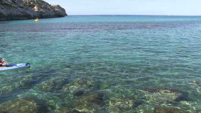 Ms Man rowing boat in sea  / Cala San Vicente, Mallorco Baleric Island, Spain