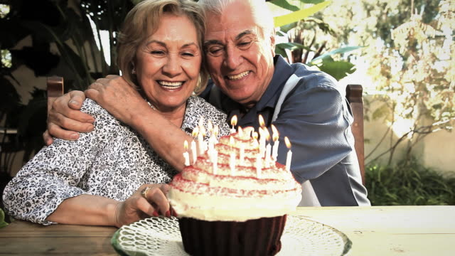 Ms Senior couple blowing out lit candles on cupcake and kissing / Los Angeles, California, USA
