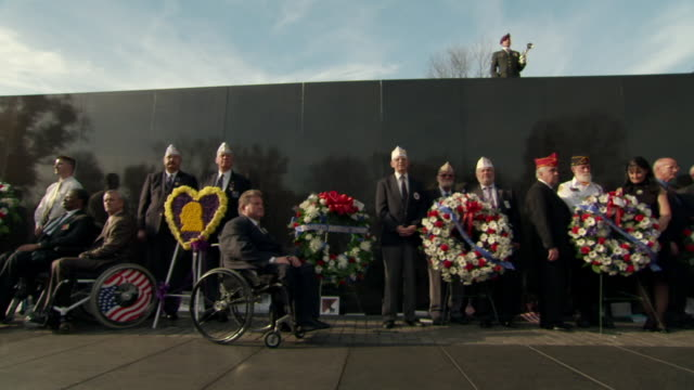 Ms Shot of Veterans in uniform including two in wheelchairs face crowd with Vietnam Veterans Memorial Wall behind them during Veterans Day event / Washington, District of Columbia, United States