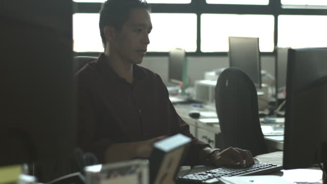 MS_Businessman typing on keyboard in big open office