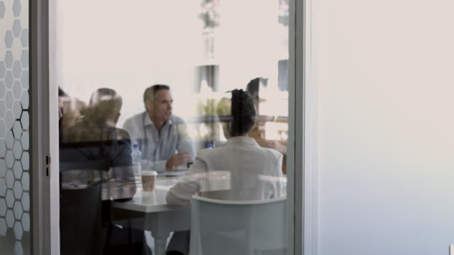 ms_businesspeople having meeting at modern office space with glasswalls - rack focus stock videos & royalty-free footage