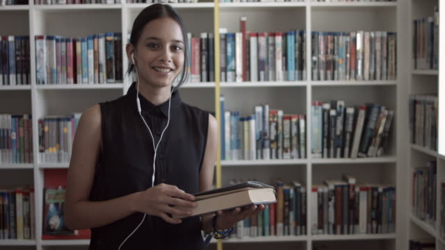 ms_female student with headphones, smiling & holding book in the library - weiblicher teenager allein stock-videos und b-roll-filmmaterial