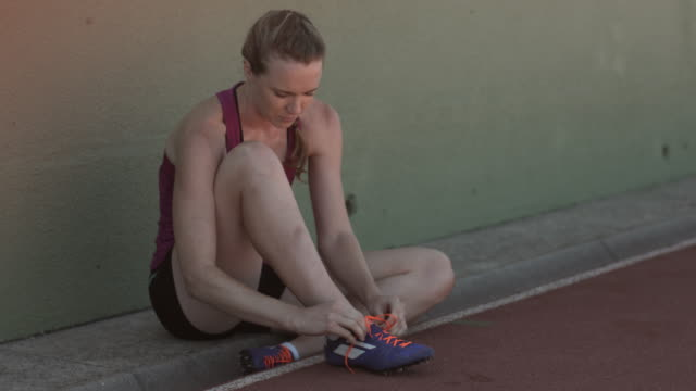 MS_Female track athlete tying shoes on track