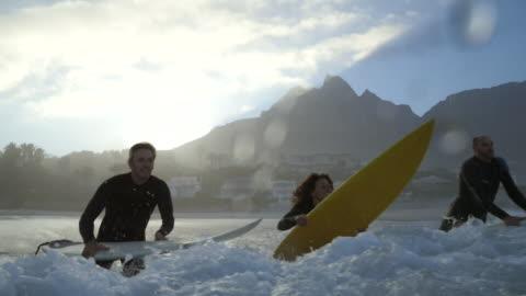 vídeos y material grabado en eventos de stock de ms_four surfers jumping out in the ocean with boards - surf