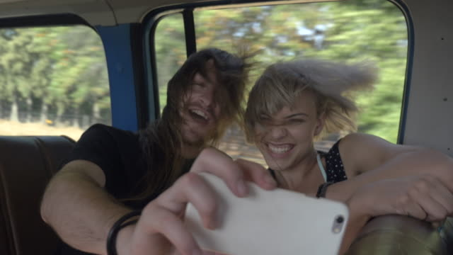 MS_Happy couple laughing with wind in the hair and making selfies on the backseat of car