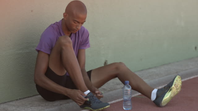 vidéos et rushes de ms_male track athlete tying shoes on track - chaussures