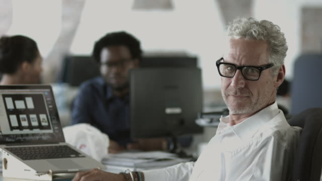 MS_Mature businessman turning from desk and smiling to camera